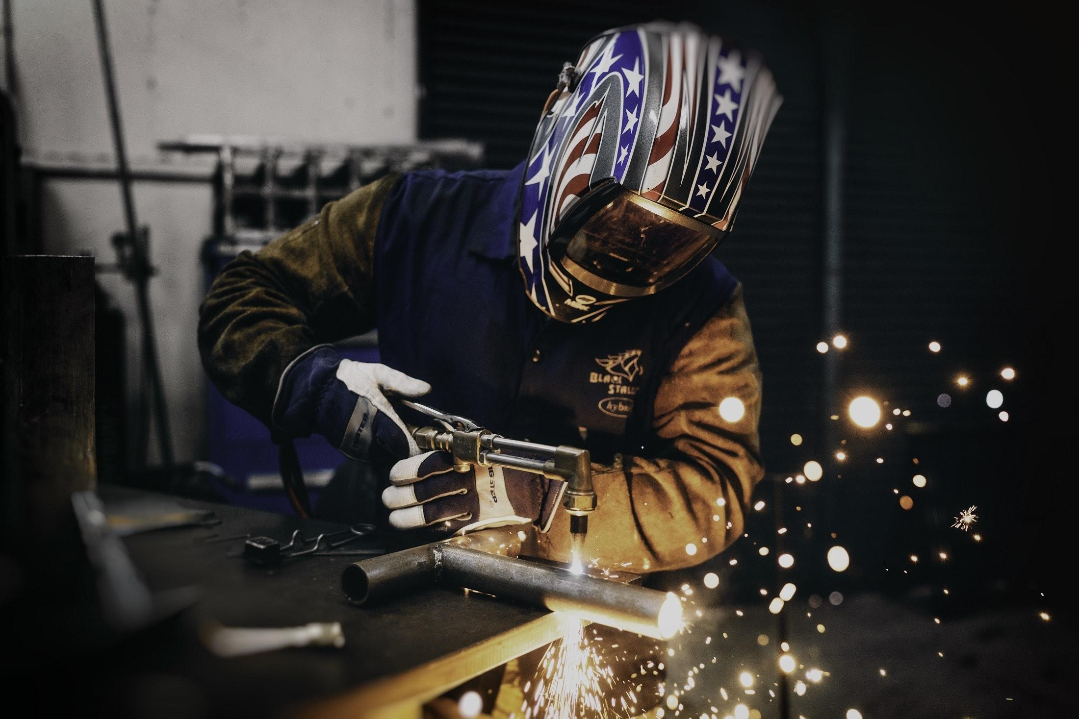 welder with American flag helmet. Welding Careers for Veterans at ETI School of Skilled Trades